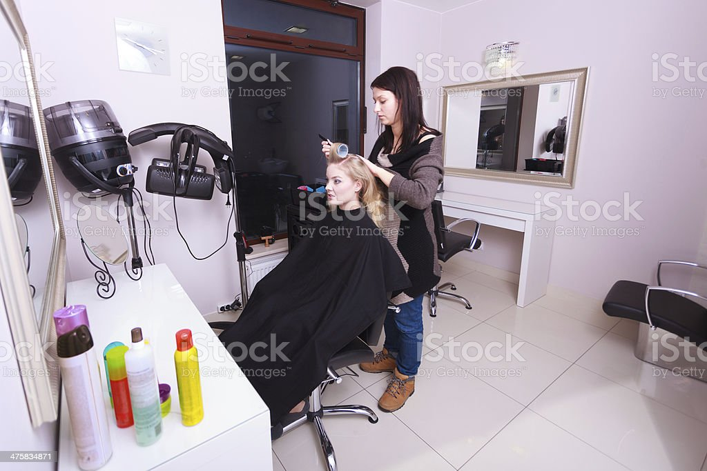 Happy blond girl hair curlers rollers by haidresser in salon royalty-free stock photo