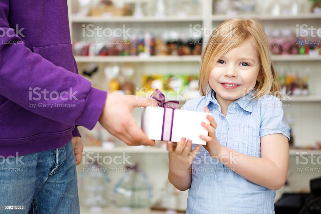 happy blond girl receiving gift in candy shop stock photo