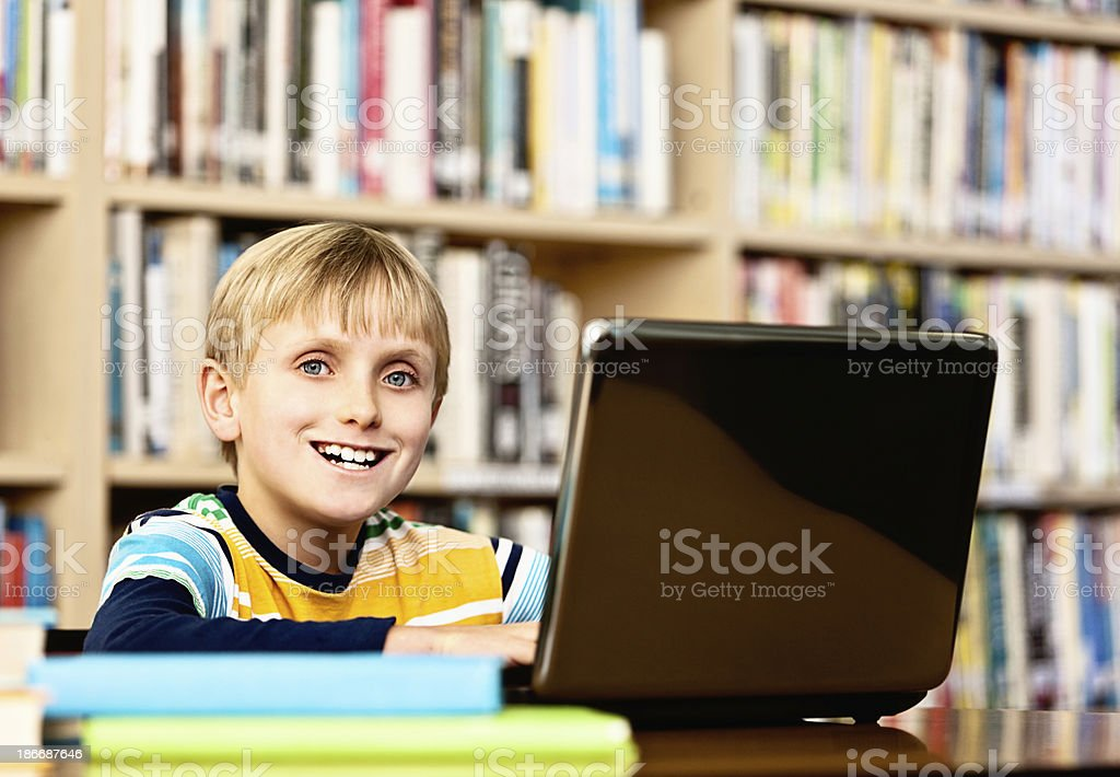 Happy blond schoolboy enjoying using laptop in library stock photo