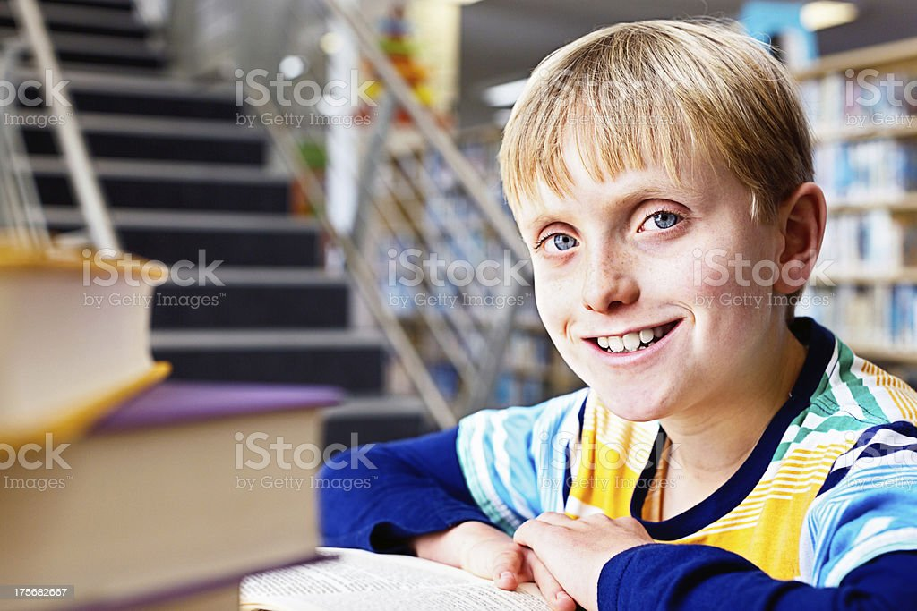 Happy blond schoolboy sitting in library smiles stock photo