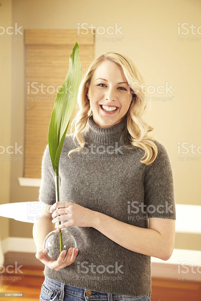 Happy blond woman holding vase with green leaf royalty-free stock photo