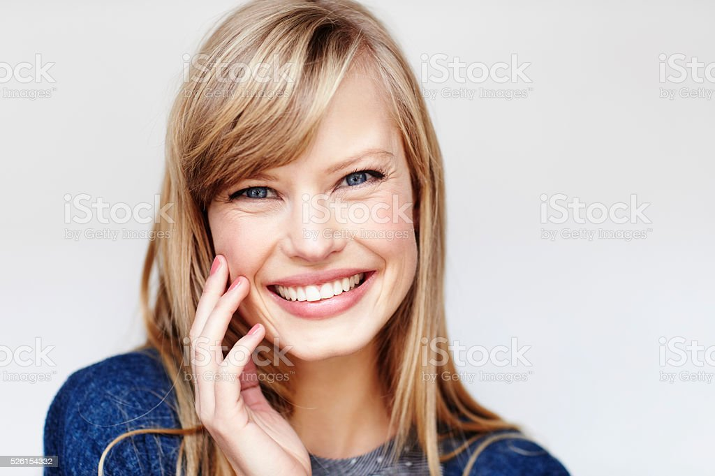 Happy blond young woman smiling, studio stock photo