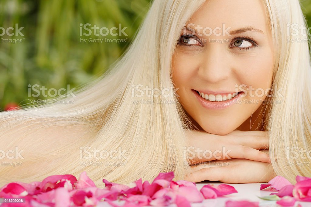 Happy blonde attractive woman with roses in a spa stock photo