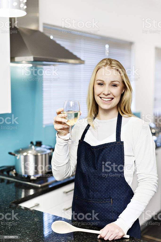 Happy blonde cooking in kitchen toasts with white wine royalty-free stock photo