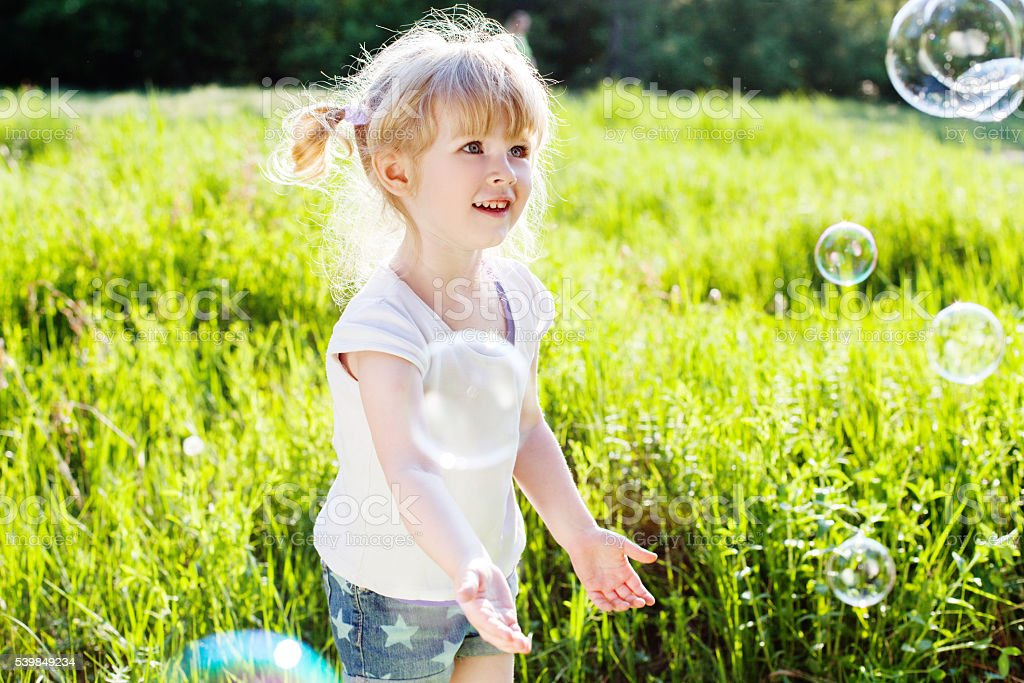 Happy blonde girl playing with bubbles. Outdoor. Nature stock photo