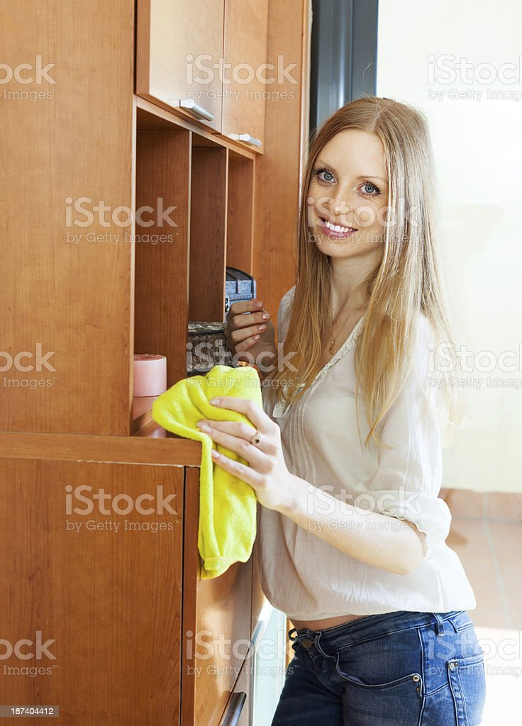 Happy blonde girl wiping the dust royalty-free stock photo