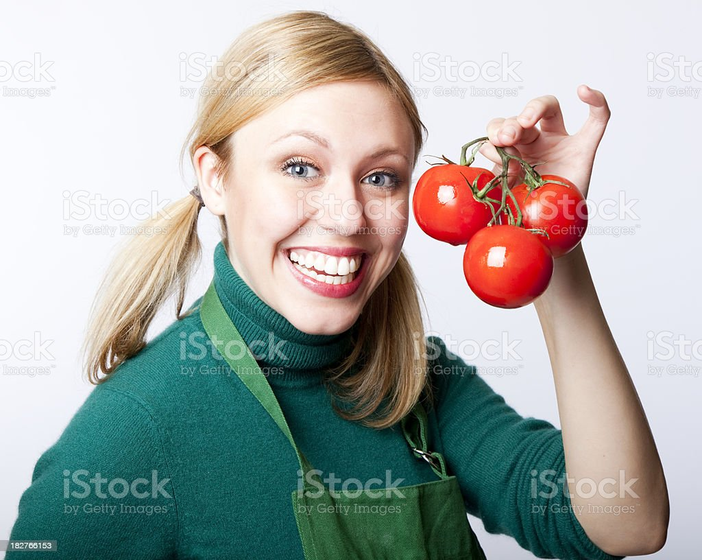happy blonde green grocer showing her tomatoes royalty-free stock photo