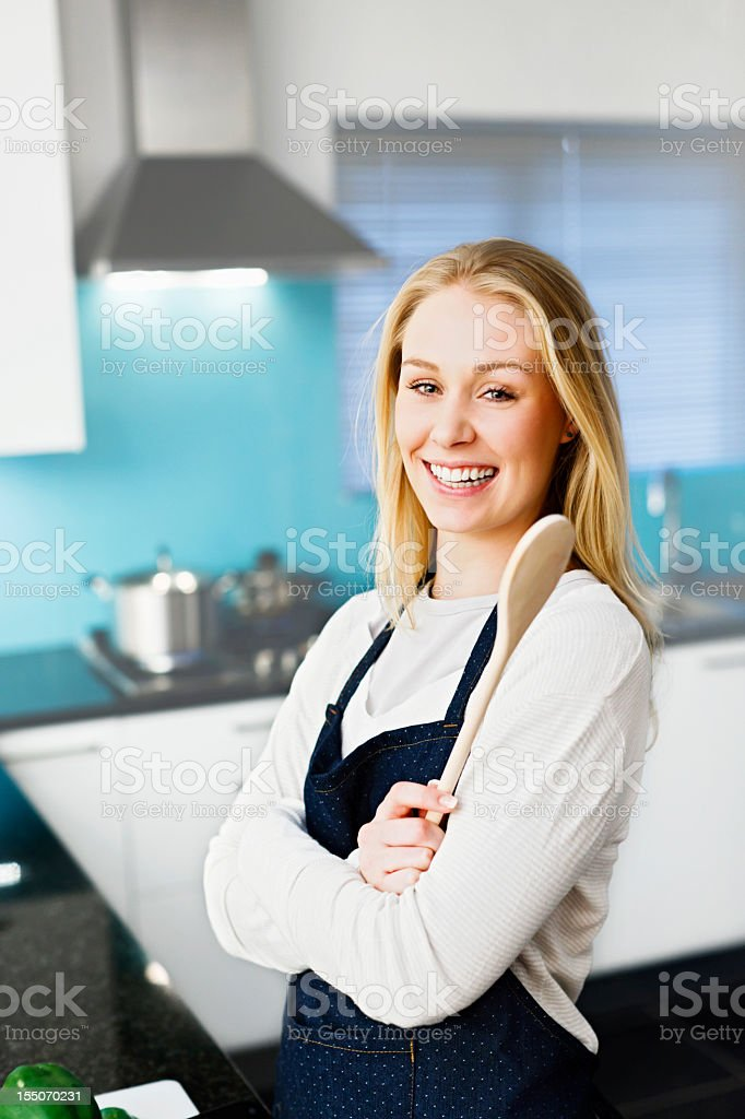 Happy blonde home maker with wooden spoon in modern kitchen royalty-free stock photo