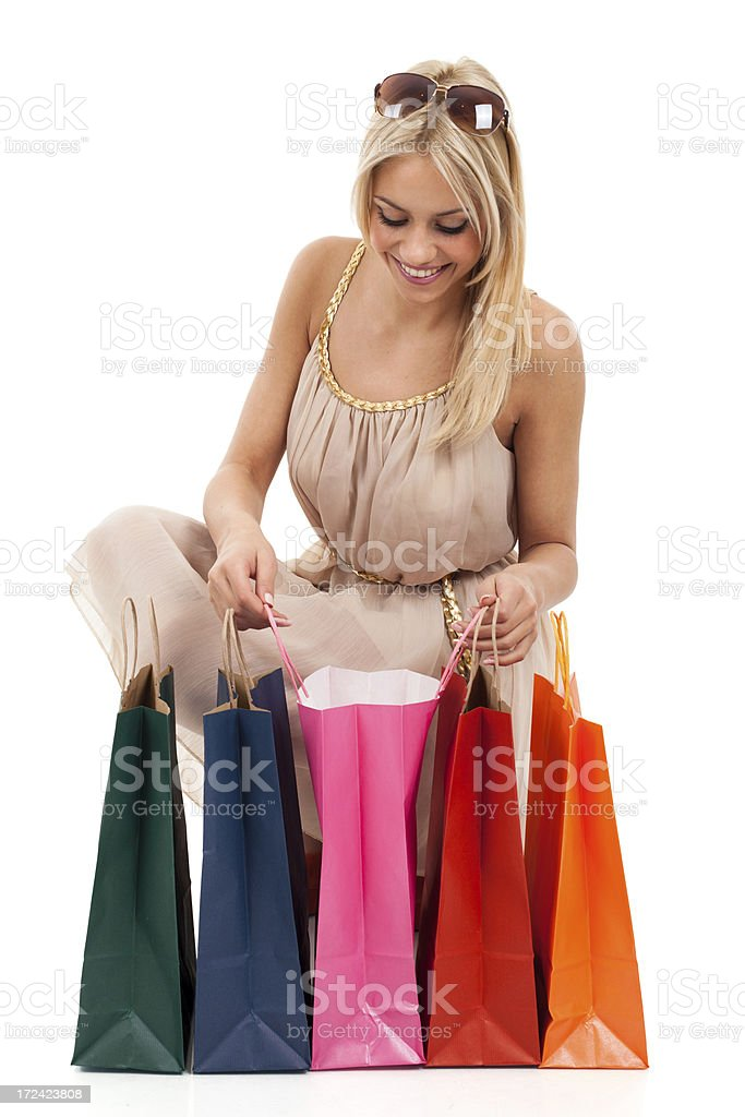 Happy blonde looking in shopping bags royalty-free stock photo
