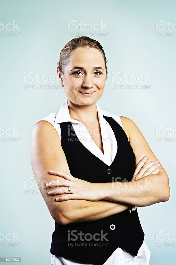 Happy blonde smiles confidently, arms folded stock photo