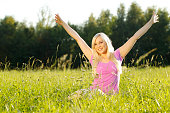 Happy blonde woman in the grass with outstreched arms