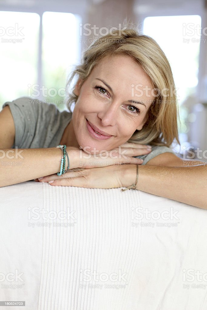 Happy blonde woman on sofa looking at camera royalty-free stock photo