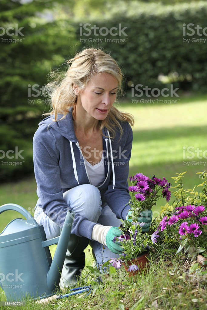 Happy blonde woman taking care flowers in garden royalty-free stock photo