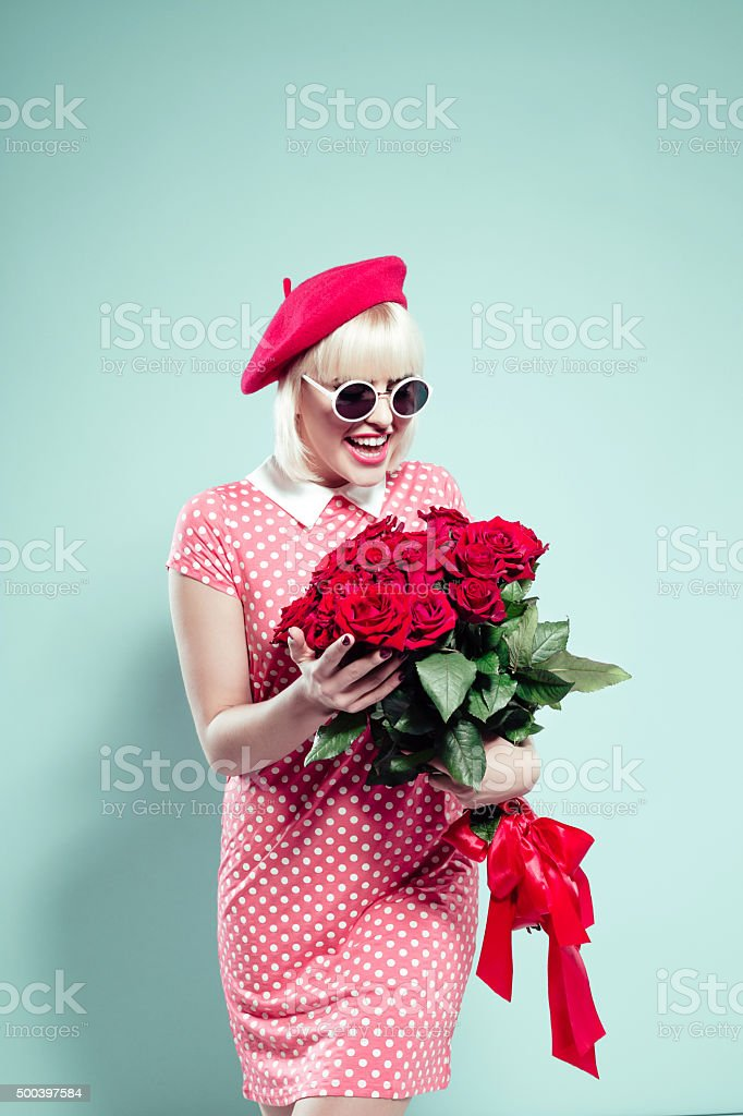 Happy blonde young woman holding bunch of red roses stock photo