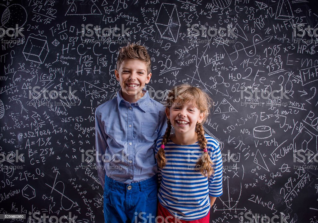 Happy boy and girl at school against big blackboard. stock photo