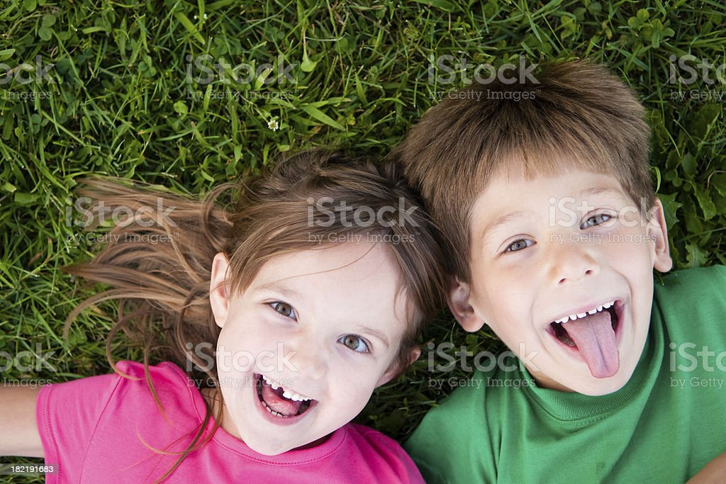 Happy Boy and Girl Lying in the Grass royalty-free stock photo