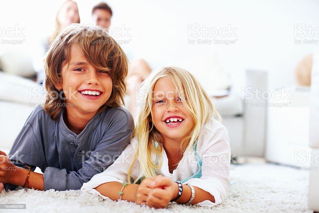 Happy boy and girl lying on floor stock photo