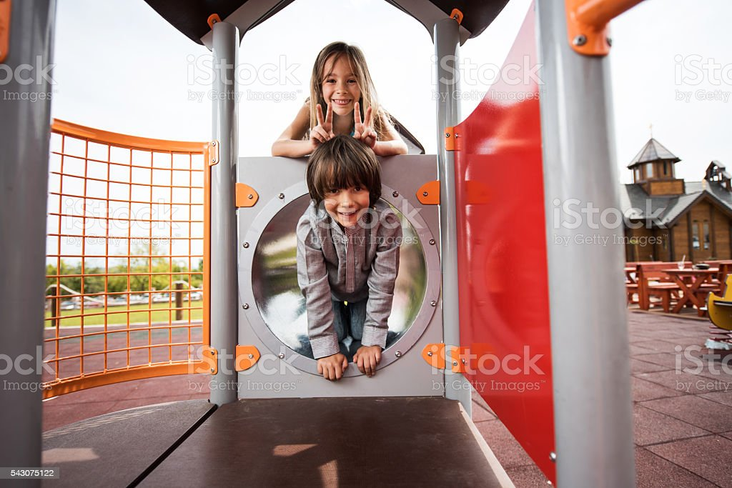 Happy boy and girl playing together at the playground. stock photo