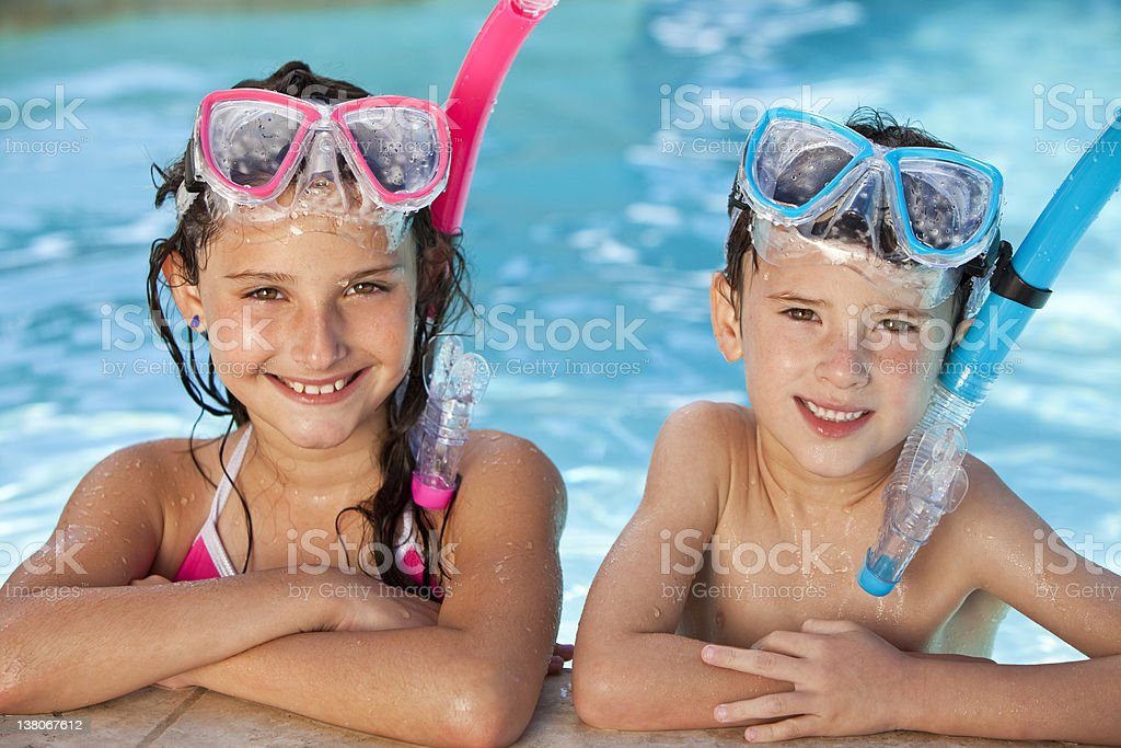 Happy boy and girl wear goggles, snorkels in pool royalty-free stock photo