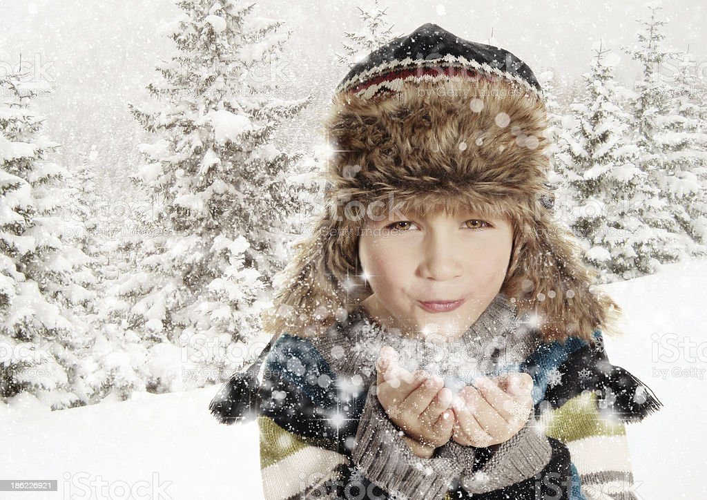 Happy boy blowing snowflakes in winter landscape stock photo