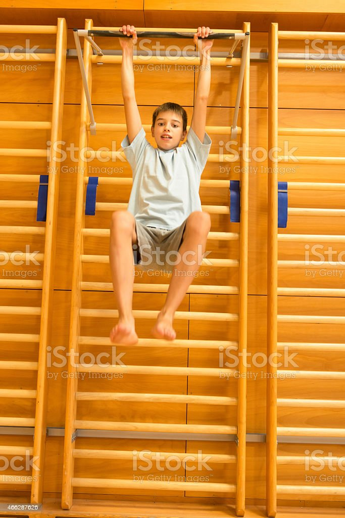 Happy Boy Climbing/Exercising on Wall Bars in School Gymnasium stock photo
