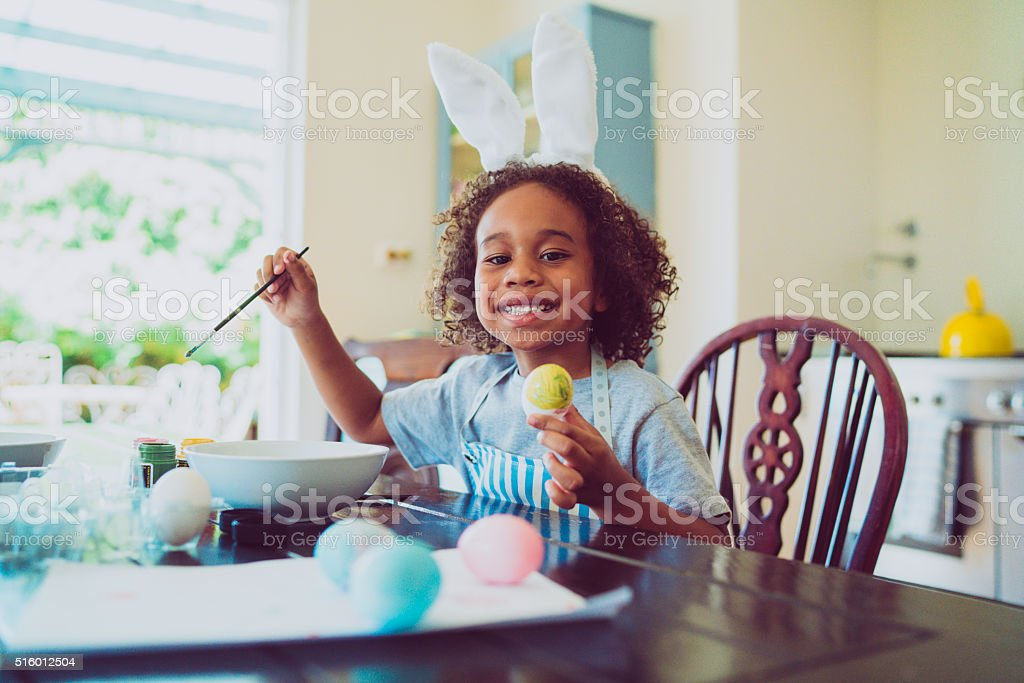 Happy boy coloring Easter egg at home stock photo