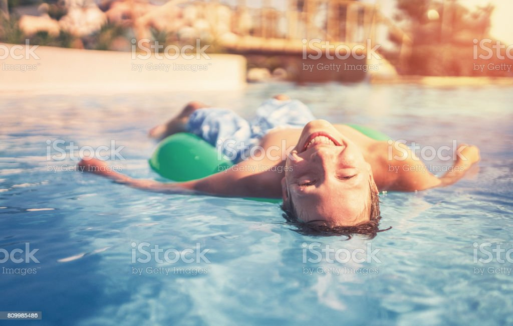Happy boy floating on swim ring in the swimming pool stock photo