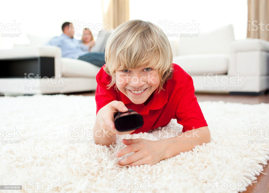 Happy boy holding a remote lying on the floor royalty-free stock photo