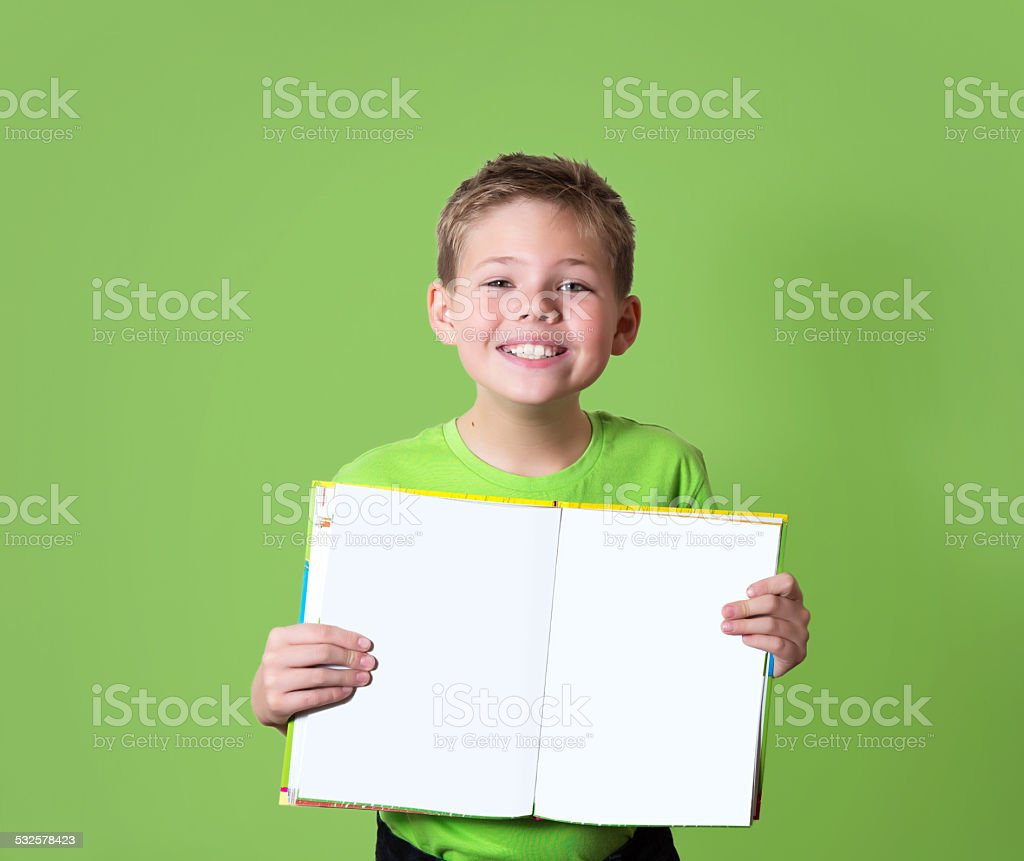 Happy boy holding book with empty copy space. Education concept. stock photo