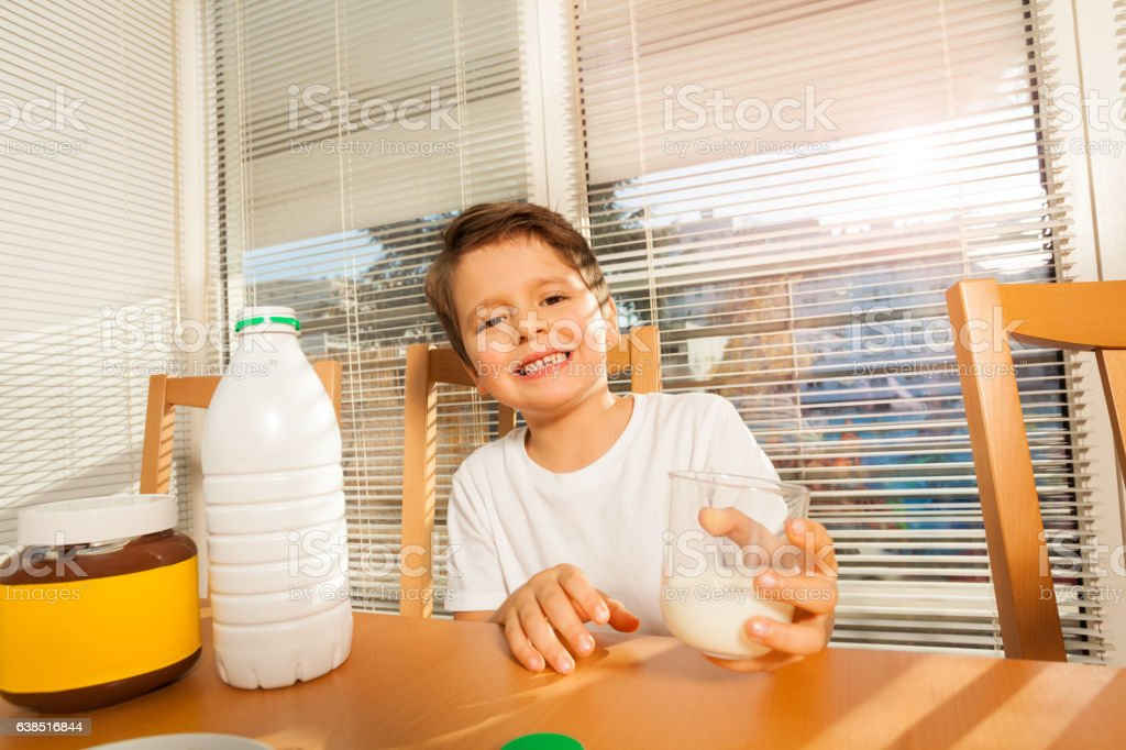 Happy boy holding glass with milk sitting at table stock photo