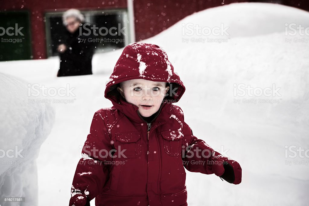 Happy Boy in a Red Jacket on a Snowy Day stock photo