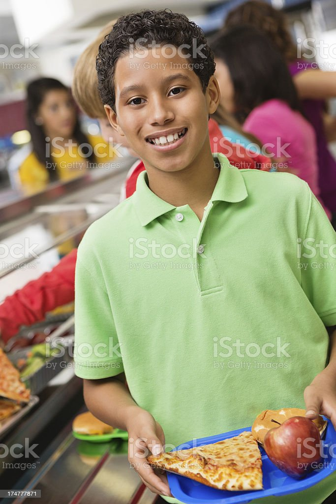 Happy boy in cafeteria lunch line with other students royalty-free stock photo