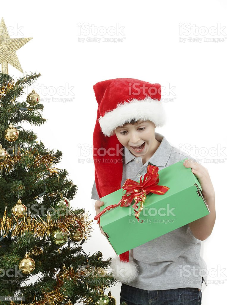 happy boy in santa hat surprised by christmas present royalty-free stock photo
