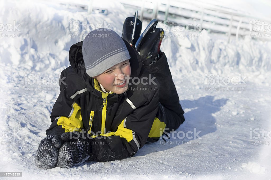 Happy boy in skates lying on ice stock photo