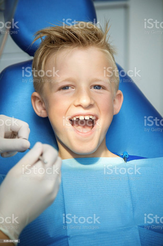 Happy boy in the dental chair stock photo