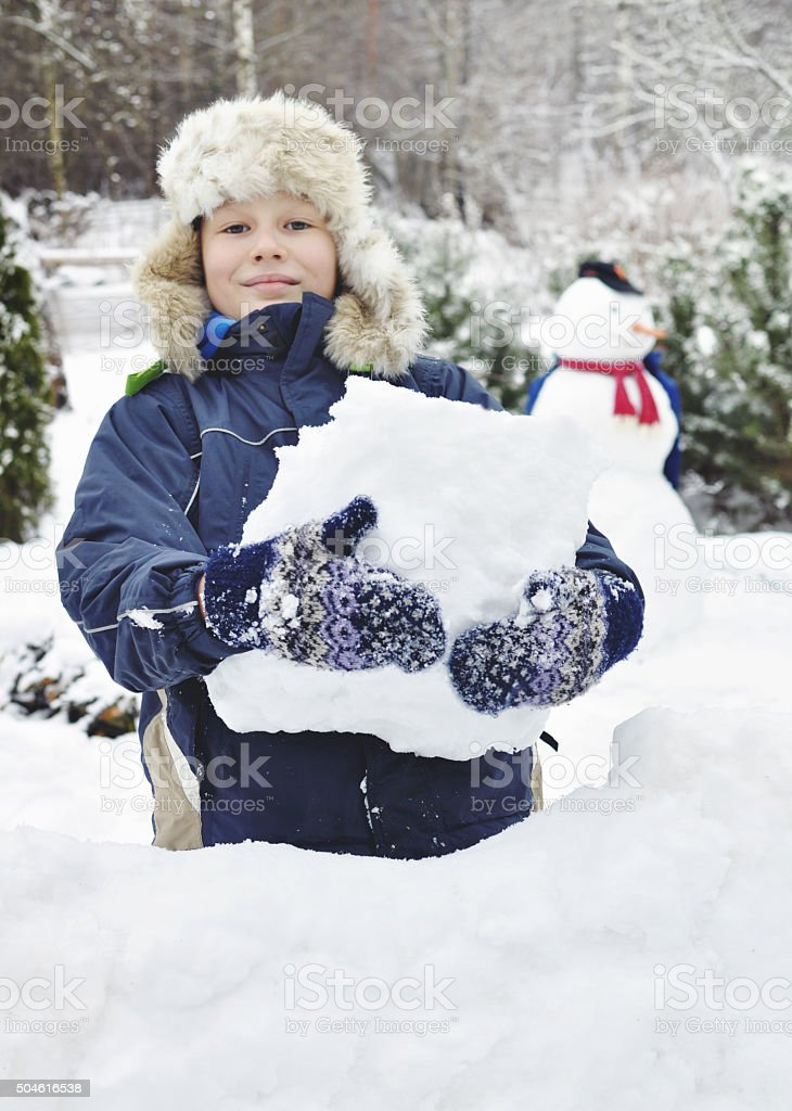 Happy boy is building a snow fort stock photo