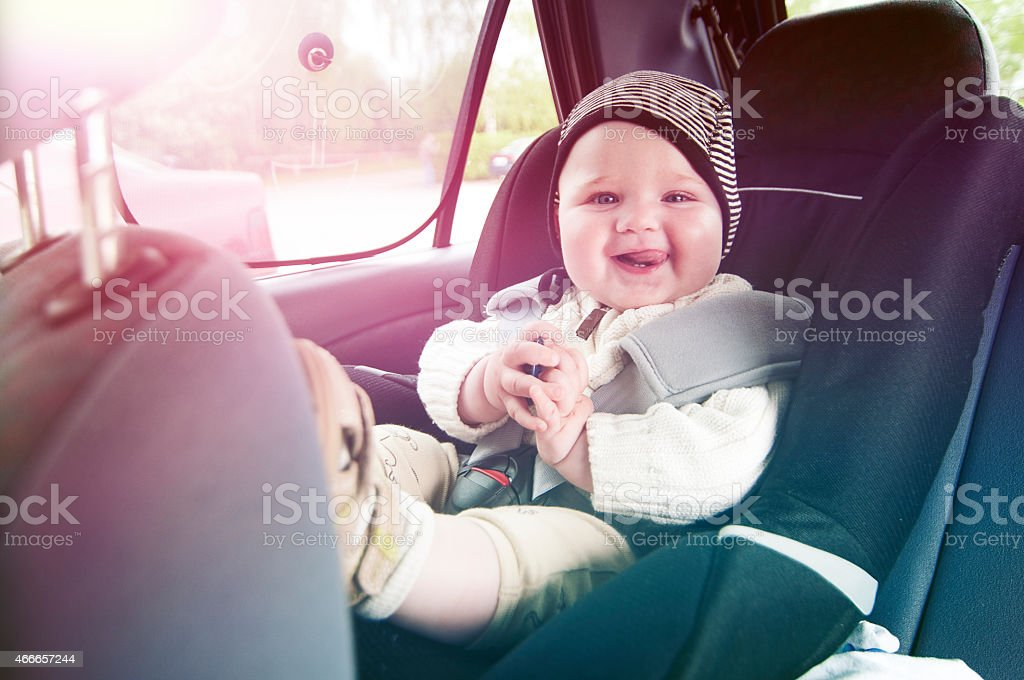 Happy boy is secure in a baby car seat stock photo