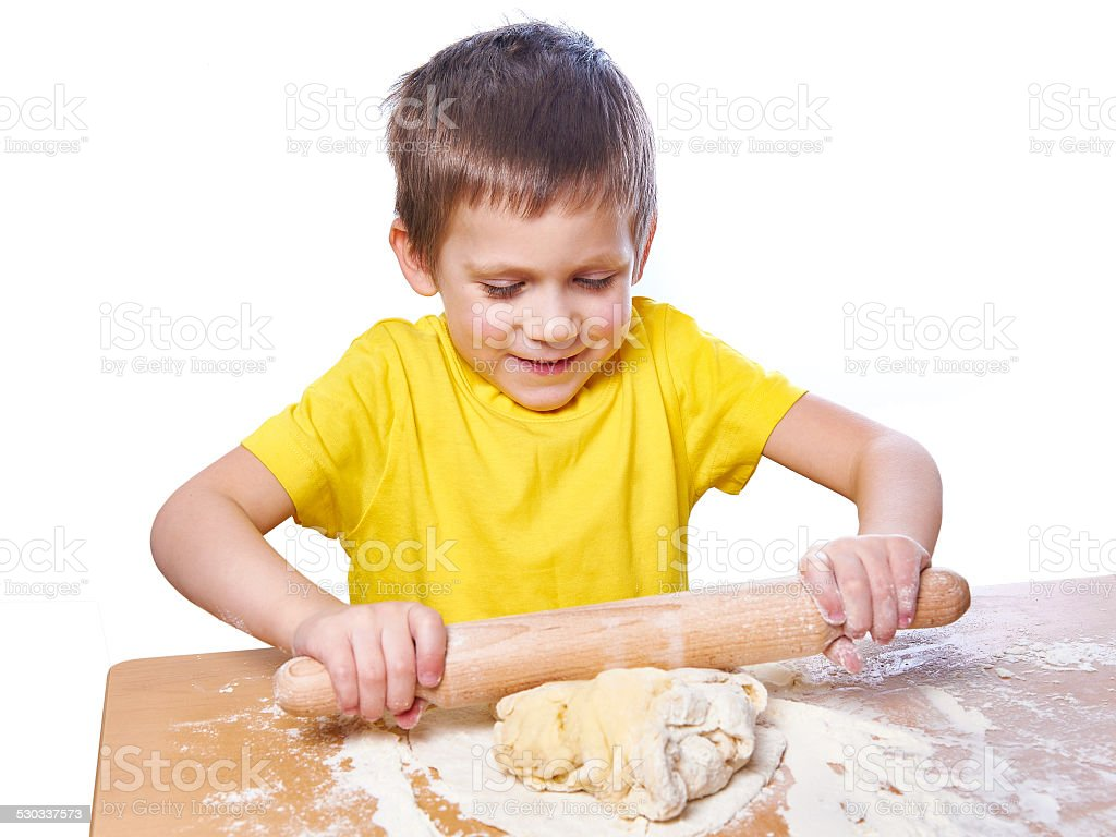 Happy boy kneads and rolling dough on kitchen table stock photo