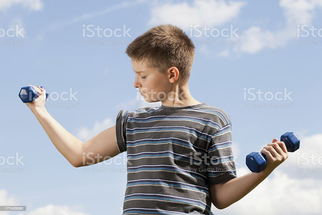 Happy boy lifting dumbbells outdoors stock photo