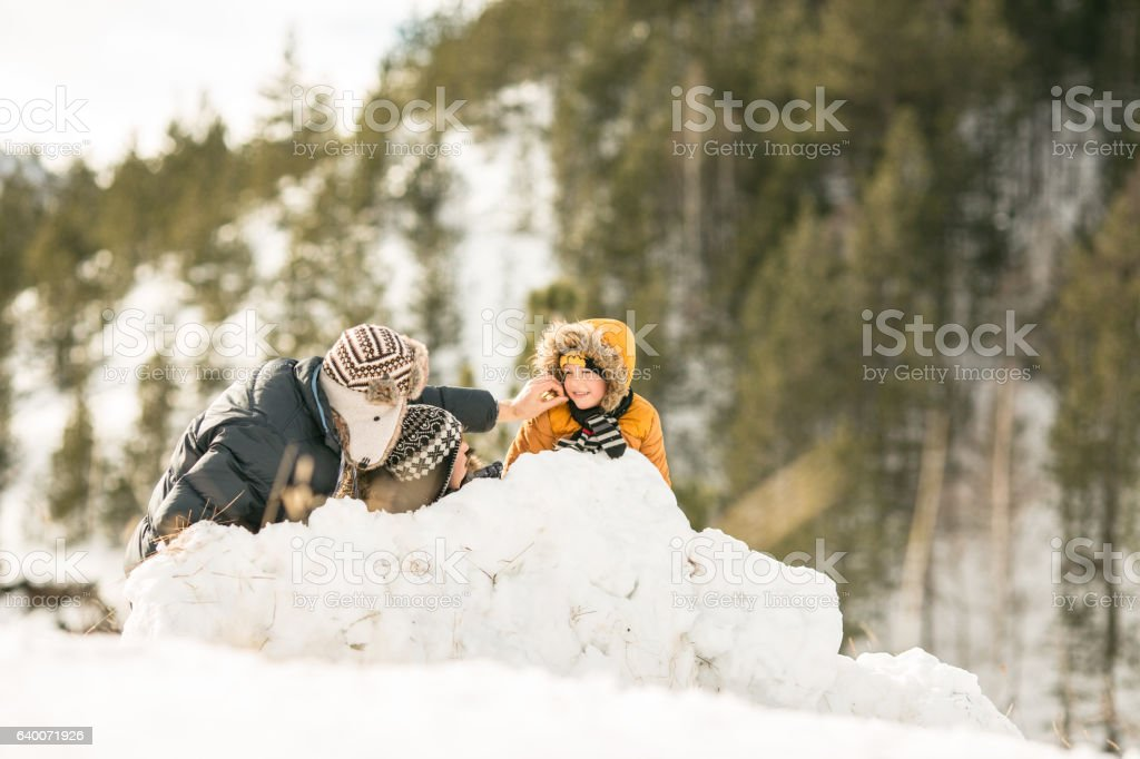 Happy boy making snowman with her family stock photo