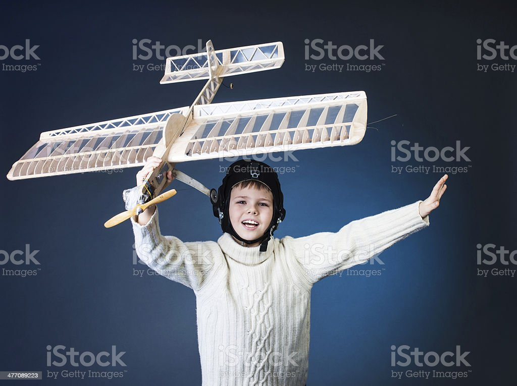 Happy boy playing with a wooden plane model. Dream. royalty-free stock photo