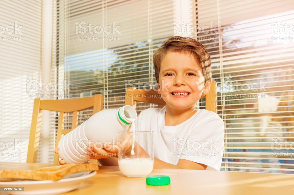 Happy boy pouring milk at breakfast in the kitchen stock photo