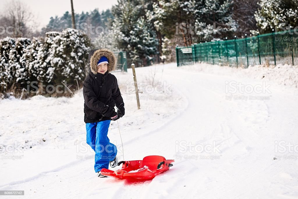 Happy boy pulling red plastic sled stock photo