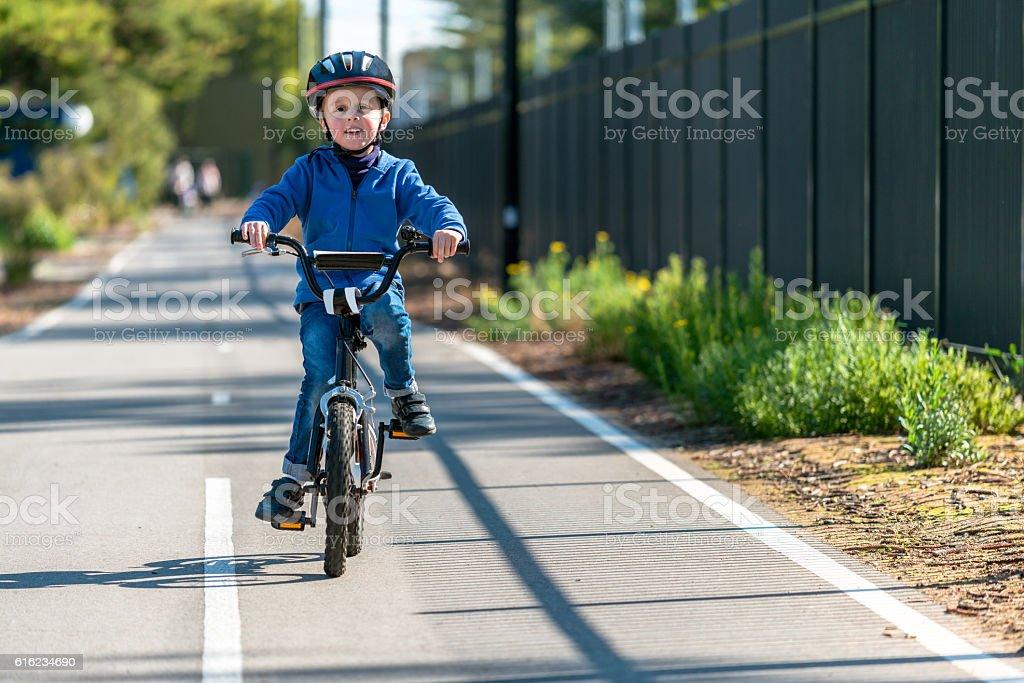 Happy boy riding his bicycle on bike lane stock photo