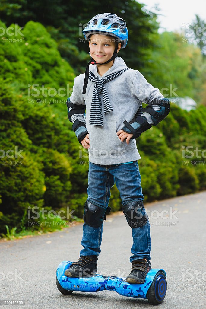 Happy boy riding on hoverboard or gyroscooter outdoor stock photo
