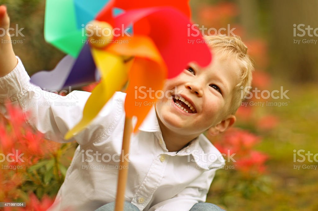 Happy Boy Spinning Pinwheel Toy in a Park stock photo