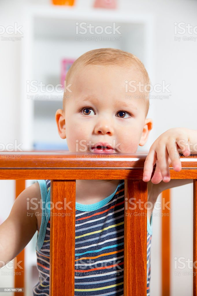 Happy boy standing in a crib stock photo