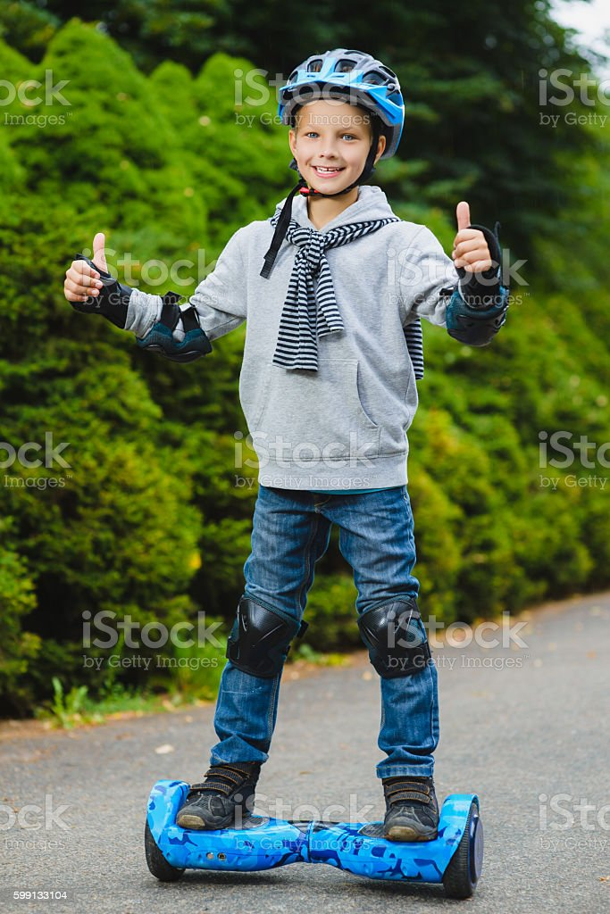 Happy boy standing on hoverboard or gyroscooter outdoor stock photo