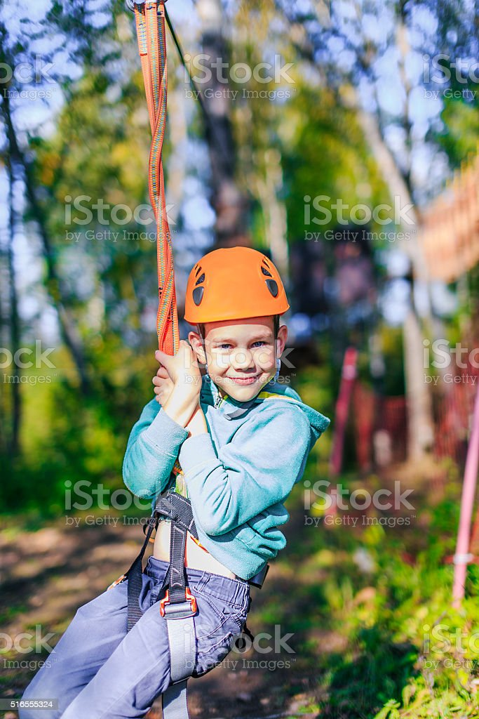 happy boy swinging on rope stock photo