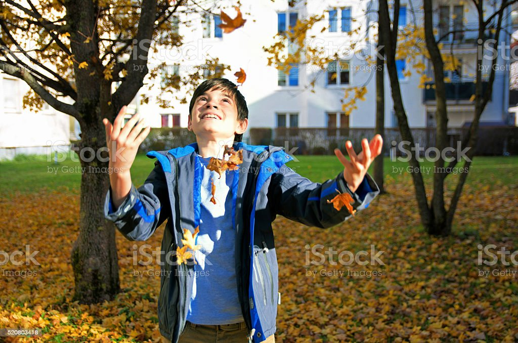 Happy boy throwing autumn leaves royalty-free stock photo